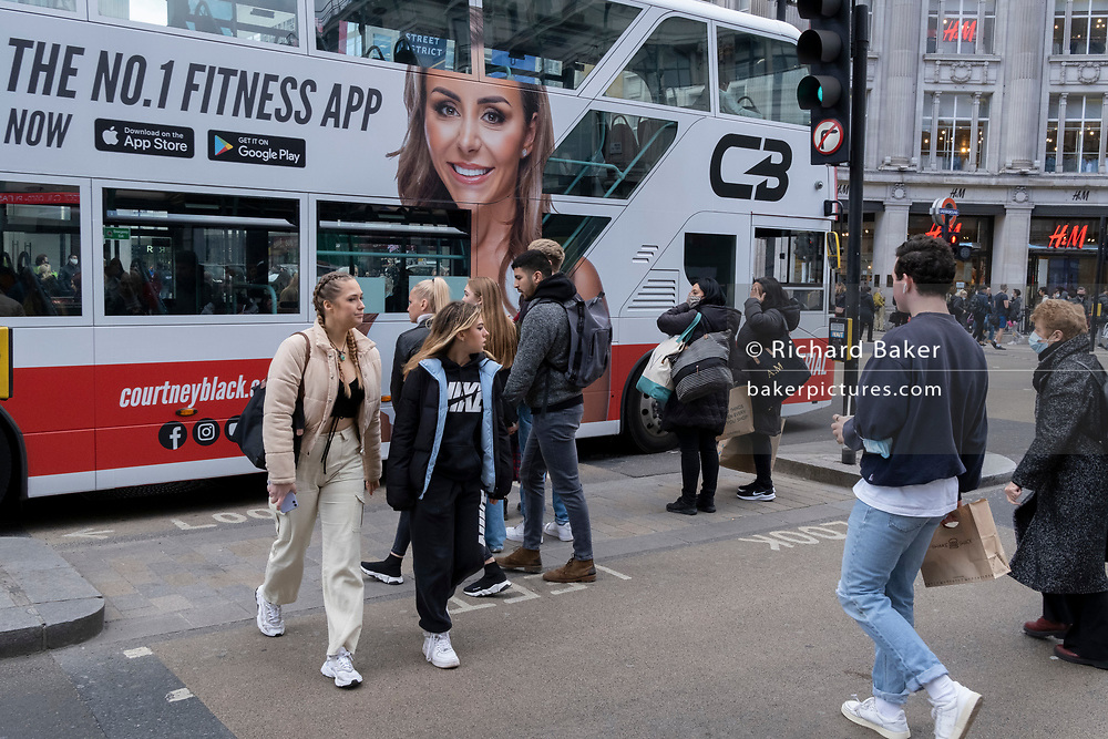 On the day that the UK government eased Covid restrictions to allow non-essential businesses such as shops, pubs, bars, gyms and hairdressers to re-open, shoppers cross regent Street next to a bus displaying a large ad for a fitness and health app with Courtney Black, on 12th April 2021, in London, England.