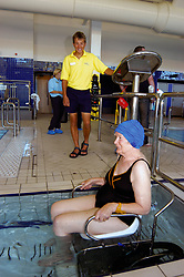 Disabled woman in wheelchair using new facilities in Council swimming pool especially adapted for disabled access to keep fit & healthy Yorkshire UK
