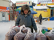 Stall with deep-frozen berries on the Yakutsk outdoor fish market. Yakutsk is a city in the Russian Far East, located about 4 degrees (450 km) below the Arctic Circle. It is the capital of the Sakha (Yakutia) Republic (formerly the Jakut Autonomous Soviet Socialist Republic), Russia and a major port on the Lena River. Yakutsk is one of the coldest cities on earth, with winter temperatures averaging -40.9 degrees Celsius.