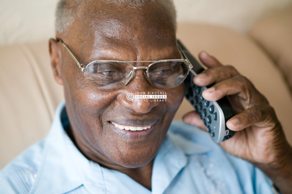 Older man smiling whilst making a telephone call,