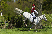 Young man rides a grey mare horse in a cross-country eventing competition, Oxfordshire, United Kingdom