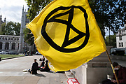 Extinction Rebellion flag at their demonstration on 4th September 2020 in London, United Kingdom. With government resitting after summer recess, the climate action group has organised two weeks of events, protest and disruption across the capital. Extinction Rebellion is a climate change group started in 2018 and has gained a huge following of people committed to peaceful protests. These protests are highlighting that the government is not doing enough to avoid catastrophic climate change and to demand the government take radical action to save the planet.