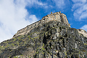 South face of 1100-year-old Edinburgh Castle on Castle Rock. Edinburgh Castle is the most besieged place in Great Britain and one of the most attacked in the world, with 26 sieges in its 1100-year-old history. Few of the present buildings pre-date the Lang Siege of the 1500s except for St Margaret's Chapel from the early 1100s, the Royal Palace, and the early-1500s Great Hall. Edinburgh is the capital city of Scotland, in Lothian on the Firth of Forth, Scotland, United Kingdom, Europe.