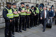 As environmental activists protest at Bank in the City of London, a City worker on his lunch hour passes a line of police officers on the 11th and final day of protests, road-blockages and arrests across London by the climate change campaign Extinction Rebellion, on 25th April 2019, in London, England.