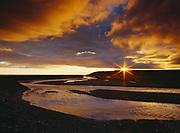 The Midnight Sun skirting the horizon beyond the mouth of Agagrak Creek, Arctic Ocean, Cape Krusenstern National Monument, Alaska.