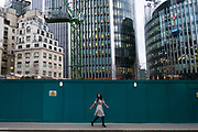 Fashionable woman turning around to look behind her as she walks past a City of London contruction site in London, England, United Kingdom. (photo by Mike Kemp/In Pictures via Getty Images)