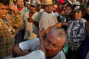The crowd watches as men fist fight in the plaza during the fiestas in Zitlala, Mexico.  In this village they  maintain the ancient tradition of fighting in jaguar masks. This is a pre-Columbian tradition in which the blood and sweat that fall to the ground are an offering to earth.  In return for their blood the people ask the gods for rain.  In Zitlala they fight each other with rope.