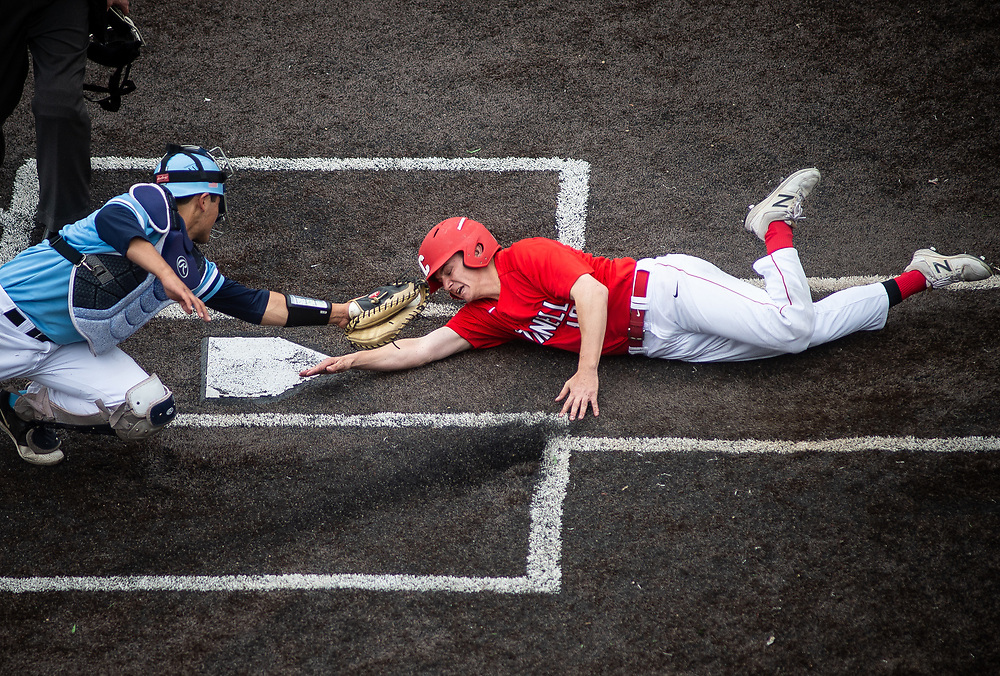 Cornell second baseman Ryan Krainz safely tags home plate, evading Columbia catcher Lane Robinette during a game at Hoy Field in Ithaca, N.Y. on May 13, 2018.