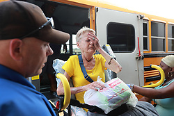 September 2, 2019, St. Mary'S, GA, USA: Glynn County school resource officer Mark Hooper, left, and school support staff member Sheree Armstrong, right, help an emotional Elizabeth Scales board a special needs school bus at Lanier Plaza as hundreds of local residents evacuate the area under mandatory evacuation ahead of Hurricane Dorian on Monday, Sept. 2, 2019, in Brunswick, Ga. (Credit Image: © TNS via ZUMA Wire)