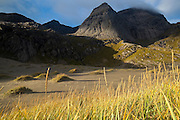 Granite cliffs rise above the sand dunes of Bunes Beach, Moskenesoya, Lofoten Islands, Norway.