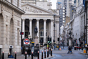 A few pedestrians and a homeless person on the junction at Bank Triangle, in front of Royal Exchange and the Bank of England, during the third lockdown of the Coronavirus pandemic, in the 'City of London', the capital's financial district, aka The Square Mile, on 2nd February 2021, in London, England.