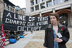 "© licensed to London News Pictures. London, UK 01/05/2012. A protester holds a red rose in front a banner which reads ""A line of tents, guards of our future"" as Occupy London protesters gathering at Paternoster Square, outside London Stock Exchange, before their march for May Day in London. Photo credit: Tolga Akmen/LNP"