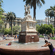 Kids playing in a fountain in Plaza de Armas in the center of Santiago de Chile.