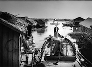 Family, who lives in a floating house, bails out boat that will tow the house out into deeper water as the water levels fall at the onset of dry season, Tonle Sap, Cambodia.
