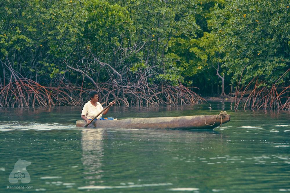 A woman traverses a lush mangrove in a dugout canoe, Kadavu island, Fiji. Kadavu is one of the least developed islands in the Fijian archipelago. It is home to about 10000 people.