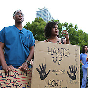 """People gather and hold signs in Lake Eola park during the """"National Moment of Silence"""" event at the Lake Eola bandshell in downtown Orlando, Florida on Thursday, August 14, 2014. In light of the recent killing of eighteen year old Mike Brown in Ferguson, Missouri, citizens across America are gathering in solidarity to hold vigils and observe a moment of silence to honor victims of suspected police brutality. (AP Photo/Alex Menendez)"""