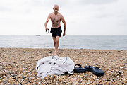 A wild swimmer walks towards his towel, glasses and shoes on the shingle, after a swim in the cold tidal waters of the Thames Estuary, on 26th July 2021, in Whitstable, England.