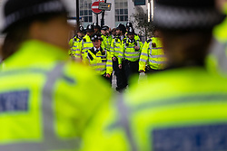 Police march towards the scene as hundreds of environmental protesters from Extinction Rebellion occupy Oxford Circus, a pink yacht being the focal point of their presence, with traffic denied access to two of London's busiest streets. London, April 16 2019.