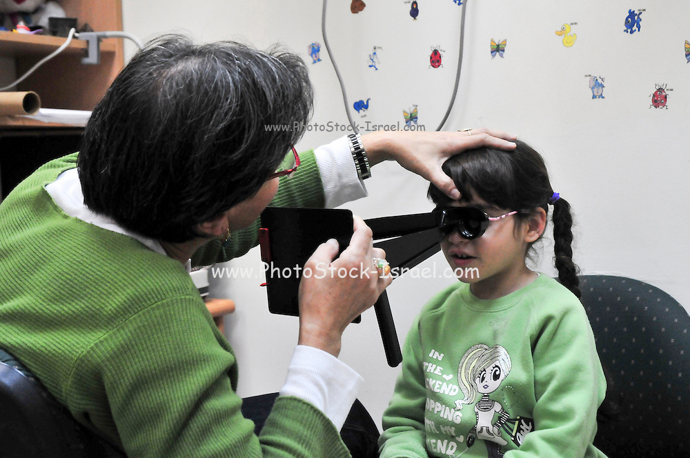 A young child of 5 having her yesy checked by an optician