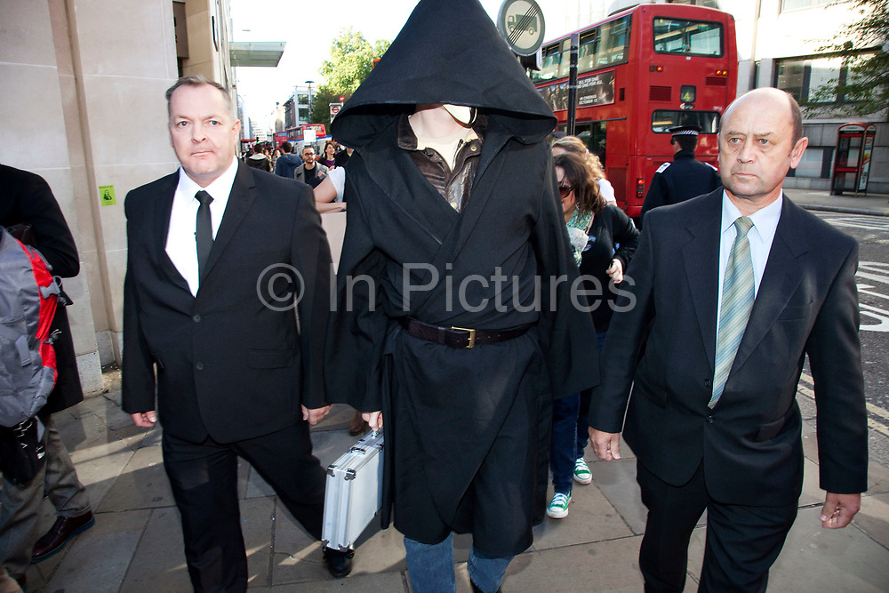 """Julian Assange at the Occupy London demonstration 15th October 2011. Seen here after arriving in a taxi with his own security, he tries to get through police lines wearing a black cape, hood and mask. He was immediately asked to take off the mask where upon he was dragged through the lines by the police, mask removed and questioned for a few minutes. He was then given a caution and released. According to the people he was with, he was just there to support the demonstration, but as usual, caused some publicity. Julian Assange is the Australian publisher and Internet activist. Editor in chief of WikiLeaks, the whistleblowing website and conduit for worldwide news leaks. Protests spread from the US with this demonstrations in London and other cities worldwide. The 'Occupy' movement is spreading via social media. After four weeks of focus on the Wall Street protest, the campaign against the global banking industry started in the UK this weekend, with the biggest event aiming to """"occupy"""" the London Stock Exchange. The protests have been organised on social media pages that between them have picked up more than 15,000 followers."""
