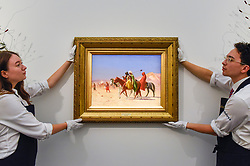 "© Licensed to London News Pictures. 11/10/2019. LONDON, UK. Technicians present ""Riders Crossing the Desert"", 1870, by Jean-Léon Gérôme, (Est GBP3-5m).  Preview of works from the Najd Collection of orientalist paintings at Sotheby's in New Bond Street, which record daily life in the historic Arab, Ottoman and Islamic worlds  All 155 paintings are on public view 11- 15 October, with 40 works to be auctioned on 22 October.  Photo credit: Stephen Chung/LNP"
