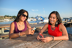 North America, United States, Washington, Kirkland, women with cell phones near dock at Marina Park.  MR