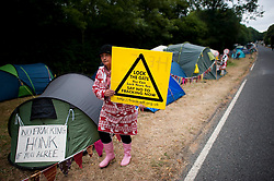 © London News Pictures. 16/08/2013. Balcombe, UK. Campaigners demonstrate outside of the entrance to the Cuadrilla drilling site in Balcombe, West Sussex which has been earmarked for fracking. Cuadrilla has temporarily ceased drilling at the site under advice from the police after campaign group No Dash For Gas threatened a weekend of civil disobedience. Photo credit: Ben Cawthra/LNP
