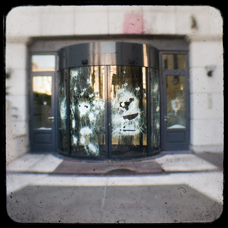 A shattered revolving door. <br /> <br /> Following the murder of a 15 year old boy, Alexandros Grigoropoulos, by a policeman on 6 December 2008 widespread riots, protests and unrest followed lasting for several weeks and spreading beyond the capital and even overseas<br /> <br /> When I walked in the streets of my town the day after the riots I instantly forgot the image I had about Athens, that of a bustling, peaceful, energetic metropolis and in my mind came the old photographs from WWII, the civil war and the students uprising against the dictatorship. <br /> <br /> Thus I decided not to turn my digital camera straight to the destroyed buildings but to photograph through an old camera that worked as a filter, a barrier between me and the city.