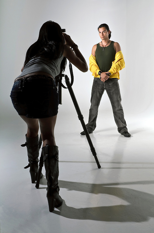Young woman photographer taking pictures of a male model in studio. Photographer woman in shilouette,