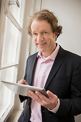 Man in suit holding digital tablet at the window