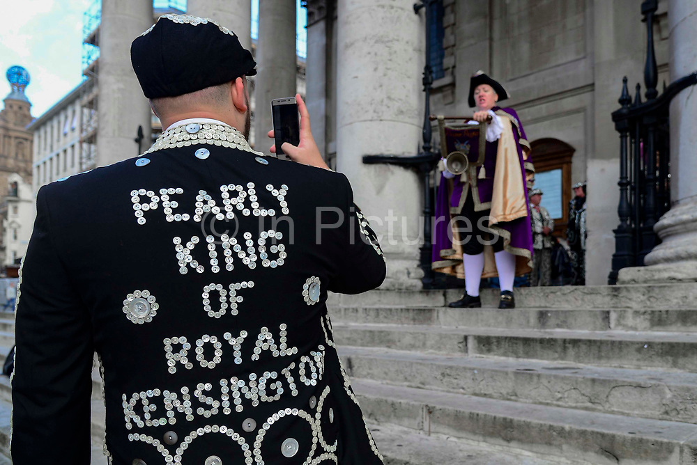 A Pearly King photographs  a town crier announcing the annual church service outside  outside St Martin-in-the-Fields church  for the Pearly Kings and Queens annual Harvest Festival on 6th October 2019 in London, United Kingdom. The tradition of the Pearly Kings and Queens originated in the 19th century when London street sweeper Henry Croft decorated his uniform and began collecting money for charity. The annual harvest festival sees Pearly Kings and Queens gather to celebrate the autumn harvest with a church service.
