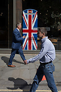 Lunchtime City workers walk past the Union Jack-themes telephone kiosk in celebrity chef Gordon Ramseys restaurant Bread Street Kitchen on the former Roman thoroughfare Watling Street, in the City of London, the capitals financial district aka the Square Mile, on 22nd August 2019, in London, England.