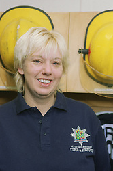 Portrait of part time female firefighter standing in front of helmets smiling,