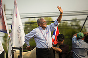 """09 DECEMBER 2013 - BANGKOK, THAILAND: SUTHEP THAUGSUBAN, former Deputy Prime Minister of Thailand and leader of anti-government protests, acknowledges the crowd as he arrives at Government House in Bangkok. Thai Prime Minister Yingluck Shinawatra announced she would dissolve the lower house of the Parliament and call new elections in the face of ongoing anti-government protests in Bangkok. Hundreds of thousands of people flocked to Government House, the office of the Prime Minister, Monday to celebrate the collapse of the government after Yingluck made her announcement. Former Deputy Prime Minister Suthep Thaugsuban, the organizer of the protests, said the protests would continue until the """"Thaksin influence is uprooted from Thailand."""" There were no reports of violence in the protests Monday. The collapse of the government leaves Thailand with an unprecedented power vacuum.      PHOTO BY JACK KURTZ"""