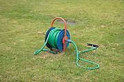 rolled up garden water hose on grass