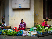 "22 DECEMBER 2017 - HANOI, VIETNAM: Vegetable sellers in a market in the old quarter of Hanoi. The old quarter is the heart of Hanoi, with narrow streets and lots of small shops but it's being ""gentrified"" because of tourism and some of the shops are being turned into hotels and cafes for tourists and wealthy Vietnamese.    PHOTO BY JACK KURTZ"