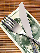 Cost of Living concept - fork and knife with Dollar banknotes