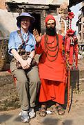 A tourist sits with a sadhu, Hindu holy man, in Kathmandu, Nepal.