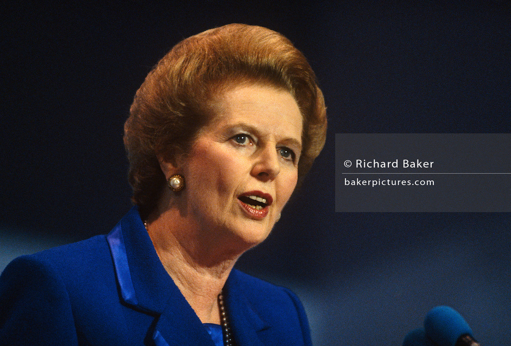 Prime Minster Margaret Thatcher is seen giving her last speech as Prime Minister at the October 1990 Conservative Party Conference in Blackpool, Lancashire before being removed by her own colleagues a few weeks afterwards. Her fighting spirit and stern expression gives her the reputation of Iron Lady with a gaze that make her opponents uncomfortable. She is wearing a favourite two-tone blue suit with wide shoulders and a pearl ear-rings. The ambient stage lights emphasize the blonde highlights in her hair.