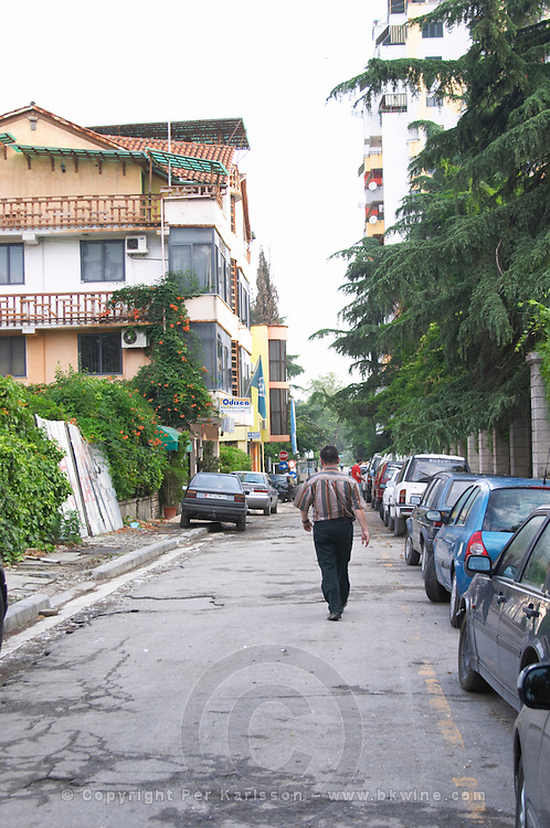 Street scene with a man walking in the middle of the street from the part of the city called The Block that used to be reserved for party dignitaries during the communist era. Tirana capital. Albania, Balkan, Europe.