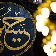 Massive calligraphy medallions in Aya Sofya with the names of Allah, the Prophet Muhammad, the first four caliphs Abu Bakr, Umar, Uthman and Ali, and the two grandchildren of Mohammed: Hassan and Hussain, by the calligrapher Kazasker İzzed Effendi (1801–1877). Originally built as a Christian cathedral, then converted to a Muslim mosque in the 15th century, and now a museum (since 1935), the Hagia Sophia is one of the oldest and grandest buildings in Istanbul. For a thousand years, it was the largest cathedral in the world and is regarded as the crowning achievement of Byzantine architecture.