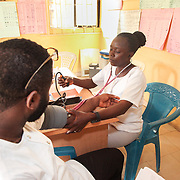 INDIVIDUAL(S) PHOTOGRAPHED: Somto (left) and Adetona Olubunmi (right). LOCATION: Ikeja Primary Health Care Center, Lagos, Nigeria. CAPTION: A nurse takes Somto's blood pressure at the Ikeja Health Center.