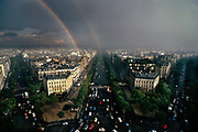 Panoramic view of skyline, taken from the top of the the Arc de Triomphe, with huge grey rain clouds and a rainbow looming over the city,10th May 1980, Paris, France.