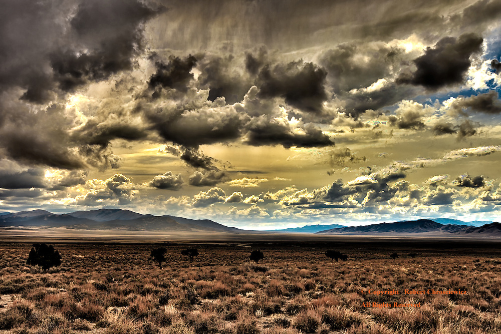Dramatic Nevada Sky: A dramatic autumn sky looms over the arid plains with mountains on the horizon and as a solitary line of well spaced trees run across the scene, Highway 93, Nevada USA.