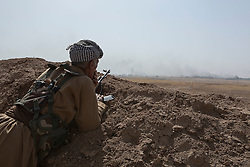 20/10/2016. Bashiqa, Iraq. A Peshmerga fighter looks towards the burning town of Tiskharab, where colleagues are clearing out Islamic State positions during an operation to retake the ISIS held town of Bashiqa Iraq, today (20/10/2016).<br /> <br /> Launched in the early hours of today with support from coalition special forces and air strikes, the attack is part of the larger operation to retake Mosul from the Islamic State, and involves both the Kurds and the Iraqi Army. The city of Bashiqa, around 9 miles north of Mosul, is one of several gateway areas that must be taken before any attempted offensive on Mosul itself.<br /> <br /> Despite the peshmerga suffering several casualties after militants fought back using mortars, heavy machine guns and snipers, the Kurdish forces were quickly taking ground with Haider al-Abadi, the Iraqi prime minister, stating that the operation to retake Mosul was progressing faster than expected. Photo credit: Matt Cetti-Roberts/LNP