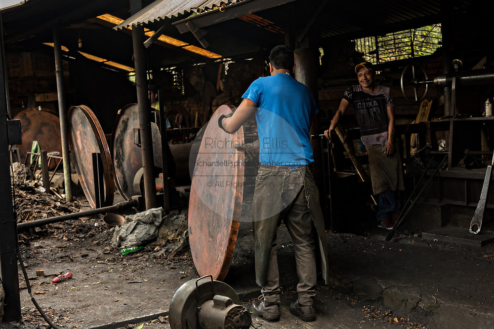An indigenous Purepecha worker moves a copper pot bottom to another stage at a copper workshop in Santa Clara del Cobre, Michoacan, Mexico. The Purepecha people have been crafting copper crafts since the 12th century.