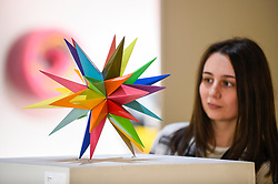 "© Licensed to London News Pictures. 04/10/2019. LONDON, UK. A staff member views ""Kaos Star"", 2019, by Okuda San Miguel at Moniker International Art Fair, an urban contemporary art fair taking celebrating its 10 year anniversary in the UK.  The fair is  place at Chelsea's Sorting Office air until 6 October 2019.  Photo credit: Stephen Chung/LNP"