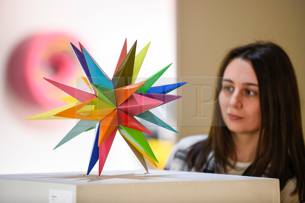 """© Licensed to London News Pictures. 04/10/2019. LONDON, UK. A staff member views """"Kaos Star"""", 2019, by Okuda San Miguel at Moniker International Art Fair, an urban contemporary art fair taking celebrating its 10 year anniversary in the UK.  The fair is  place at Chelsea's Sorting Office air until 6 October 2019.  Photo credit: Stephen Chung/LNP"""