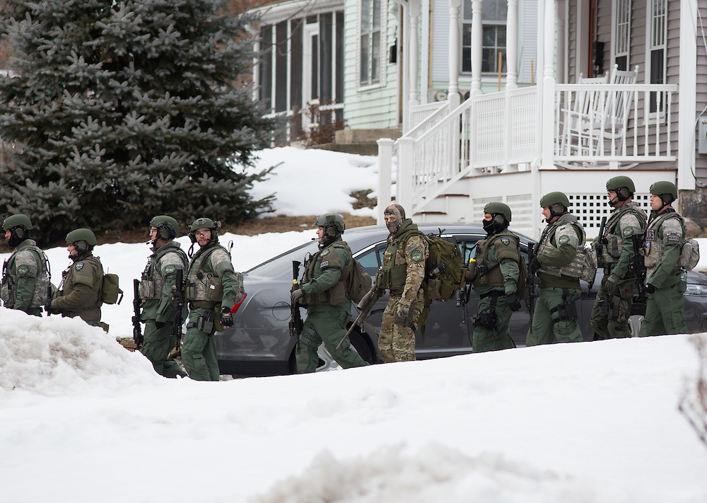 Dedham, MA 03/07/2014<br /> A column of Metro SWAT officers returns to their vehicles at the conclusion of a standoff on Leonard St in East Dedham on Friday afternoon.<br /> Alex Jones / www.alexjonesphoto.com