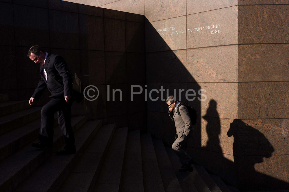 Amid by deep shadows, two male commuters climb the steps of number 1 London Bridge, a development by the John S. Bonnington Partnership, a 10-storey section clad in pink granite and stainless steel. The office complex was completed in 1986. London Bridge's history stretches back to the first crossing over Roman Londinium, close to this site and subsequent wooden and stone bridges have helped modern London become a financial success.